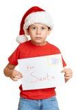 Concepto de la Navidad de las vacaciones de invierno - muchacho en sombrero con la letra a santa en blanco aislado Fotografía de archivo