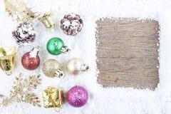 Concepto de la Navidad Decoración de la Navidad en nieve con la parte posterior de madera Imágenes de archivo libres de regalías