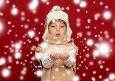 Concepto de la Navidad del invierno - muchacha en el sombrero y el suéter que soplan en el PA Foto de archivo