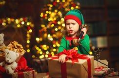 Concepto de la Navidad Funcionamiento del niño del duende, hablando en el teléfono fotografía de archivo libre de regalías