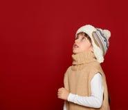 Concepto de la Navidad - la muchacha en sombrero y el suéter en fondo rojo miran para arriba Foto de archivo