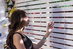 Concepto de la Navidad La luz brillante a través de un enrejado de madera blanco cae en la cara de una muchacha hermosa con el pe Imagen de archivo libre de regalías