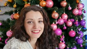 Concepto de la Navidad, morenita rizada hermosa que sonríe en el fondo de un árbol de navidad creativo adornado Cierre para arrib almacen de video
