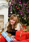 Concepto de la Navidad Muchacha feliz con los regalos por la chimenea Foto de archivo