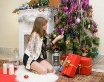 Concepto de la Navidad Muchacha feliz con los regalos por la chimenea Imagenes de archivo