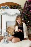 Concepto de la Navidad Muchacha hermosa por la chimenea con las velas Imagen de archivo