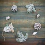 Concepto de la Navidad o del Año Nuevo con los conos, la decoración y el abeto del pino en fondo de madera Endecha plana, visión  Fotos de archivo