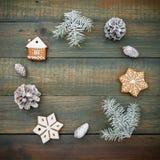 Concepto de la Navidad o del Año Nuevo con los conos, el pan de jengibre y el abeto del pino en fondo de madera Endecha plana, vi Imagenes de archivo