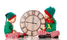 Concepto de la Navidad Pequeño ayudante del duende dos de Papá Noel con la ISO del reloj foto de archivo libre de regalías