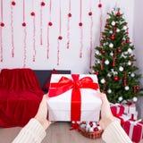 Concepto de la Navidad y del Año Nuevo - caja de regalo en la mano masculina en decoros Fotos de archivo