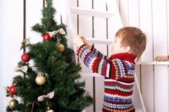 Concepto de la Nochebuena, niño que adorna el árbol de navidad Fotos de archivo