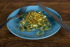 Concepto de la pérdida de peso con cierre para arriba de las píldoras de la dieta en la placa Imagen de archivo