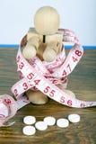 Concepto de la pérdida de peso con el hombre de madera envuelto en una cinta métrica y píldoras de la dieta imagen de archivo libre de regalías