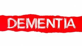 Concepto de la palabra de la demencia Texto de la demencia que aparece detrás del papel rasgado rojo foto de archivo libre de regalías