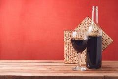 Concepto de la pascua judía del día de fiesta con el vino y el matzoh en la tabla de madera sobre fondo rojo Imagen de archivo