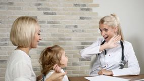 Concepto de la pediatría La madre joven y su pequeña hija bonita visitan a médicos de cabecera Pediatra ENT amistoso Niño metrajes