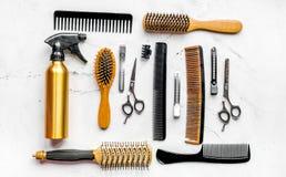 Concepto de la peluquería con las herramientas del peluquero en la opinión superior del fondo blanco Imagen de archivo