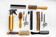 Concepto de la peluquería con las herramientas del peluquero en la opinión superior del fondo blanco Fotos de archivo libres de regalías