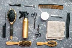 Concepto de la peluquería con las herramientas del peluquero en la opinión superior del fondo gris Fotos de archivo libres de regalías