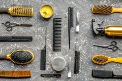Concepto de la peluquería con las herramientas del peluquero en la opinión superior del fondo gris Foto de archivo libre de regalías