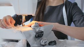 Concepto de la pequeña empresa y de la afición Ropa de diseñador de la mujer joven que trabaja en una máquina de coser en su estu almacen de metraje de vídeo