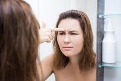 Concepto de la piel del problema - mujer hermosa que mira el espejo en baño Imágenes de archivo libres de regalías