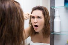 Concepto de la piel del problema - mujer que mira el espejo en cuarto de baño Foto de archivo libre de regalías