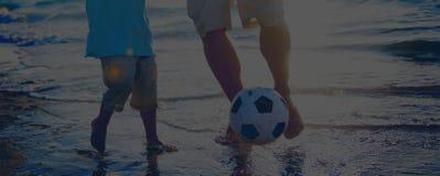 Concepto de la playa de Son Football Playing del padre imagen de archivo