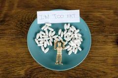 Concepto de la pérdida de peso con las píldoras blancas y la estatuilla de madera en una placa azul Imágenes de archivo libres de regalías