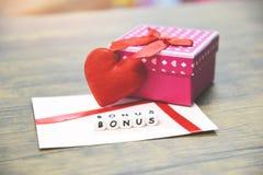 Concepto de la prima/prima anuales de la tarjeta en el sobre de papel con sorpresa de la caja de regalo y el corazón rojo fotografía de archivo