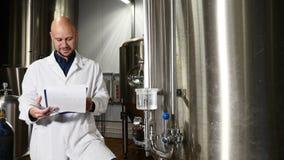 Concepto de la producción de la cerveza Escritura atenta del trabajador del mantenimiento en el tablero en la cervecería El emple almacen de metraje de vídeo