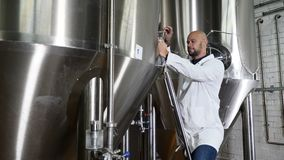 Concepto de la producción de la cerveza Escritura atenta del trabajador del mantenimiento en el tablero en la cervecería El emple metrajes