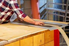 Concepto de la profesión, de la carpintería, de la artesanía en madera y de la gente - carpintero que trabaja con el tablón de ma Imagenes de archivo