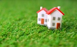 Concepto de la propiedad de las propiedades inmobiliarias con dos peque?as casas del juguete en una hierba artificial verde fotografía de archivo libre de regalías