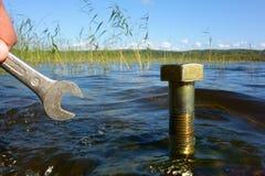 Concepto de la protección de agua: fingeres masculinos que sostienen una herramienta próxima un aumento grande del agua Foto de archivo libre de regalías