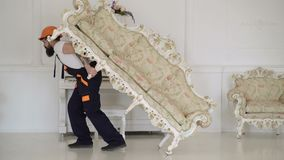 Concepto de la relocalizaci?n El mensajero entrega los muebles en caso de se mueve hacia fuera, relocalizaci?n Hombre con la barb almacen de metraje de vídeo