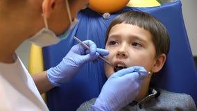 Concepto de la salud Un muchacho está en la silla del dentista con sus ojos llenos de rasgones que consiguen al tratamiento denta almacen de video