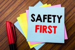 Concepto de la seguridad primero del texto del aviso de la escritura para la advertencia segura escrita en el papel de nota pegaj Foto de archivo libre de regalías