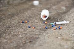 Concepto de la sobredosis de droga Píldoras e inyección Fotos de archivo