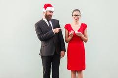 Concepto de la sonrisa sarcástica y de la mofa Hombre que señala los fingeres en la mujer y el smilin foto de archivo libre de regalías