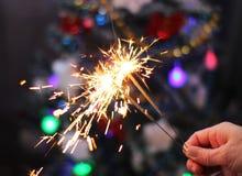 Concepto de la suavidad y de la falta de definición Mano femenina que sostiene un primer ardiente de las bengalas Año Nuevo y la  Imagen de archivo libre de regalías