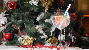 Concepto de la tabla del Año Nuevo y de la Feliz Navidad Cóctel del banquete en un vidrio con una paja en ella con un árbol de la metrajes