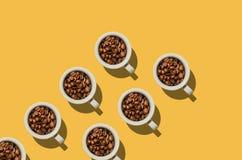 Concepto de la taza Tazas blancas con los granos de café en fondo amarillo Fotografía de archivo libre de regalías