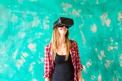 Concepto de la tecnología, de VR, del entretenimiento y de la gente - mujer joven feliz con las auriculares de la realidad virtua Foto de archivo libre de regalías