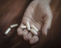 Concepto de la tenencia ilícita de drogas, mano pasiva en piso con las píldoras derramadas Fotos de archivo
