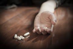 Concepto de la tenencia ilícita de drogas, mano pasiva en piso con las píldoras derramadas Foto de archivo