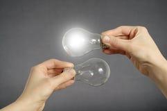 Concepto de la toma de decisión, manos con las bombillas Foto de archivo libre de regalías
