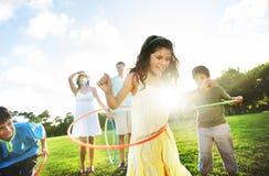 Concepto de la unidad de Hula Hooping de la familia entera al aire libre Imágenes de archivo libres de regalías
