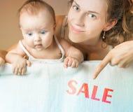 Concepto de la venta con la mamá y el bebé que mienten en la manta blanca Imagen de archivo