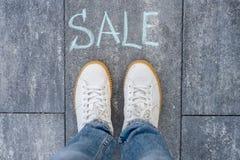Concepto de la venta a continuación con los pies de la mujer en la carretera de asfalto con el texto imagen de archivo